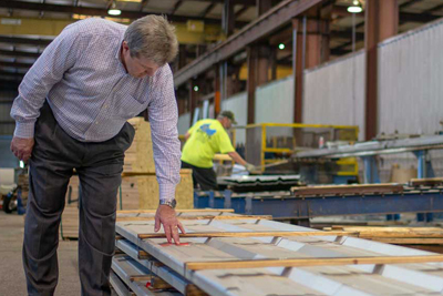 CEO Steve Browning inspects a stack of metal wall panels at the Vulcan Steel metal building manufacturing plant.