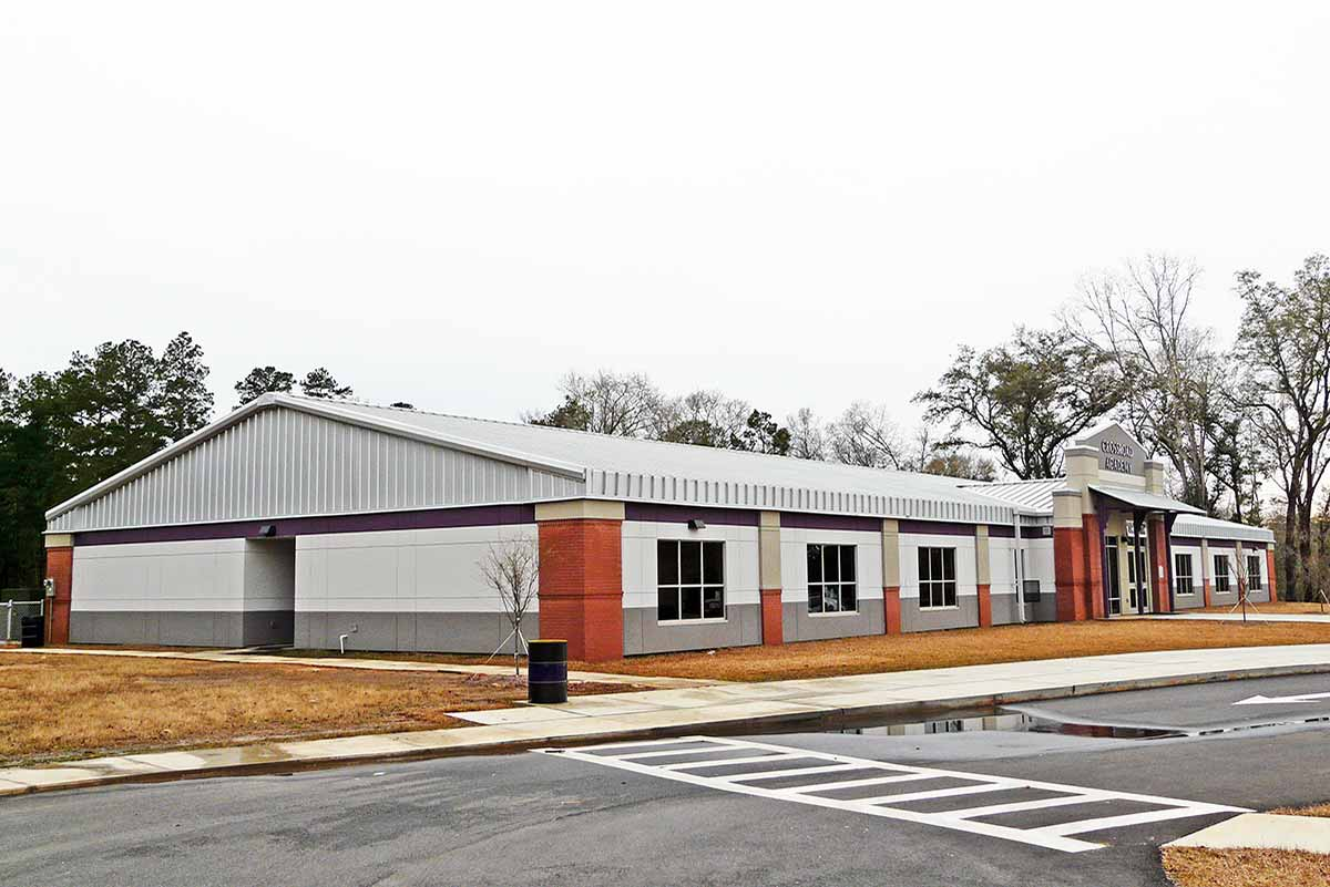Crossroad Academy Charter School has brick corner accents and a band of purple encircling the metal building's exterior.