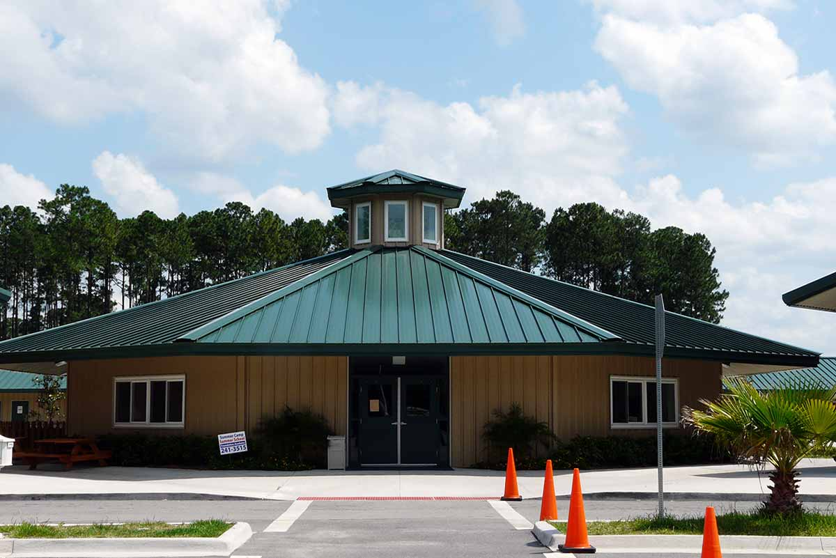 Florida's Foundation Academy is a tan, octagon-shaped metal building with a cupola atop a green standing seam roof.
