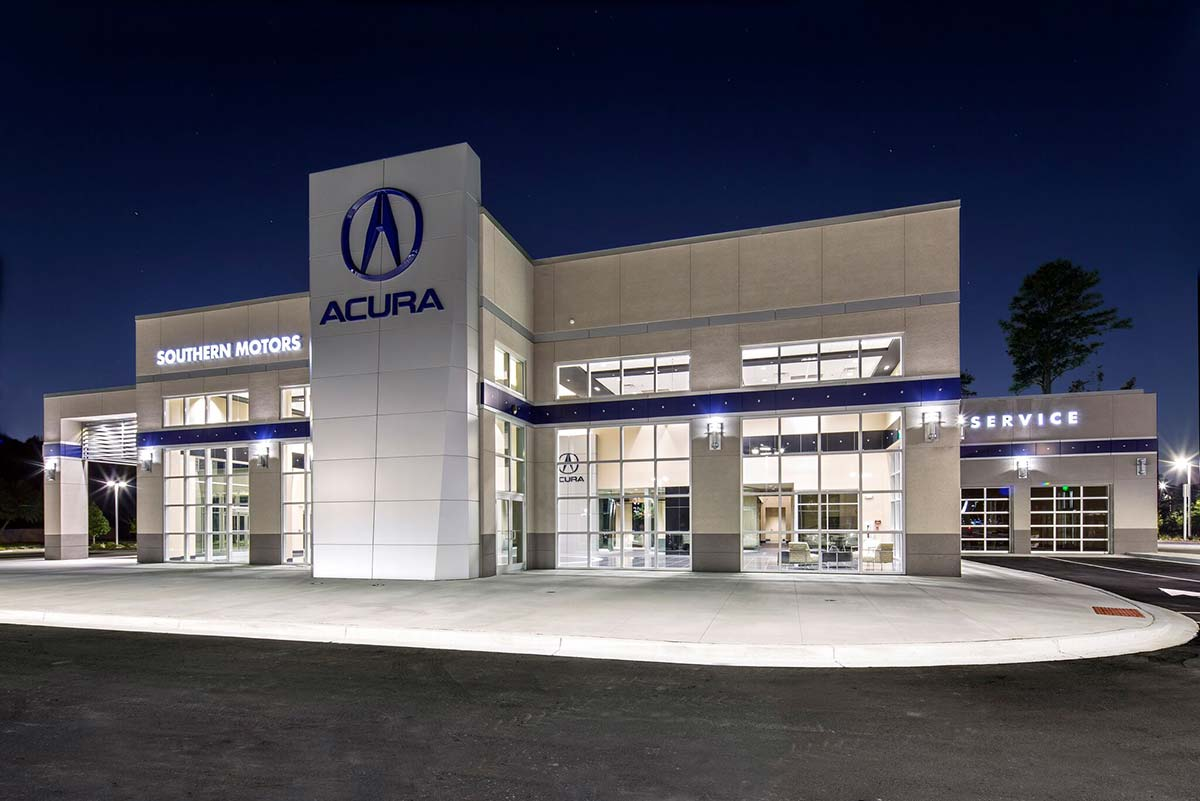 Southern Motors Acura dealership in Georgia at night with light emanating from showroom windows of a metal building system.
