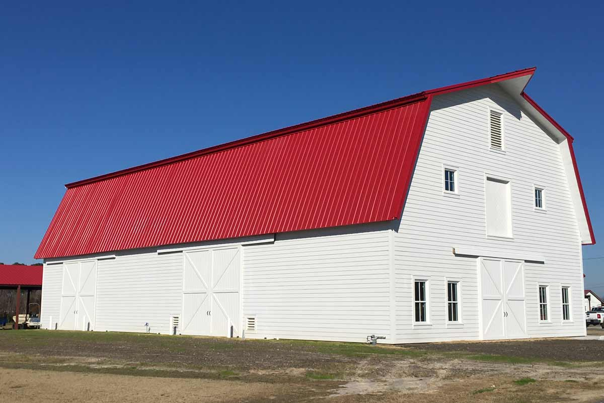 This 5100 square foot gabrel style metal barn is 42 feet high at its peak and topped with 24-gauge PBR Kynar roof coated in bright red.